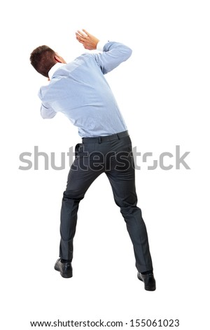 Back view of shocked and scared young business man. Holds hands upwards. Rear view. Isolated over white background