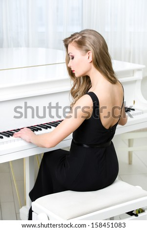 Back view of woman in black dress sitting and playing piano. Concept of music and creative hobby