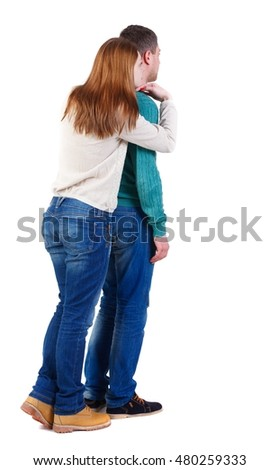 Back view of young embracing couple (man and woman) hug and look into the distance. Boy and girl hugging watching how the event.