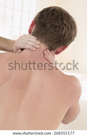 Back view of young man holding neck in pain