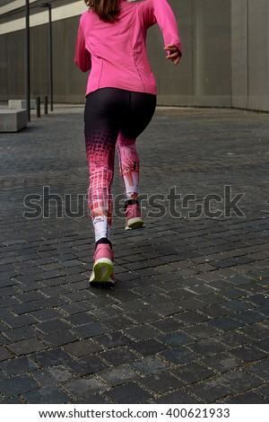 Back view of young woman running on the street