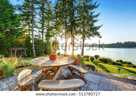 Back yard of waterfront house with rustic wooden table set, beautiful water view at sunset. Northwest, USA