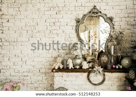 Background brick wall with a mirror. Toys and figurines on the mantel. Festive Christmas interior