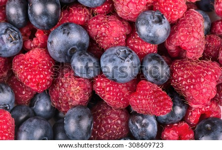 Background of scattered raspberries and blueberries closeup