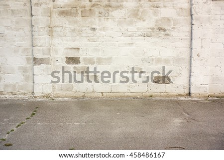 Background of white brick wall texture with part of asphalt