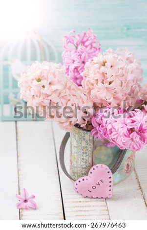 Background with fresh pink hyacinths in vase, little pink heart in ray of light  on white wooden planks against turquoise wall. Selective focus.