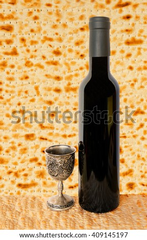 Background with Jewish unleavened bread, bottle of wine and silver cup as foreground for celebration of Jewish Passover
