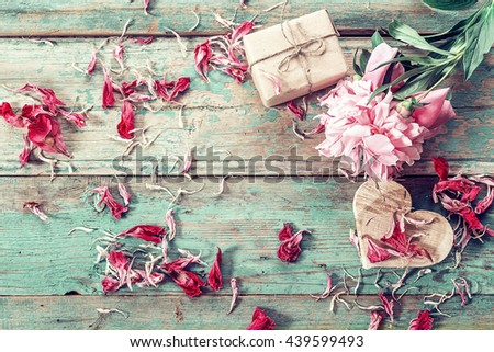 Background with pink peony, peonies petals, gift box and a wooden heart on old green boards. Place for text. Top view.