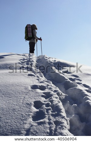 backpacker moving up in winter mountain under blue sky