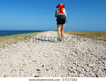 Backpacker walking on road near sea