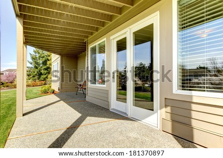 Backyard walkout deck with concrete floor. View of slide doors and windows