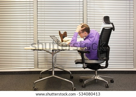 bad sitting posture at workstation - man with legs on desk