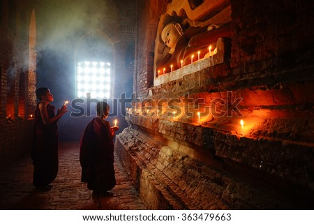 BAGAN, MYANMAR - Dec 11: Monk burning candles in front of Buddha statue inside pagoda on Dec 11, 2015 in Bagan. Monks with light and Buddha are highlighted of Bagan.
