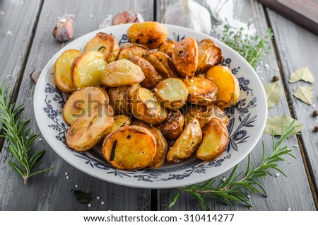 Baked potatoes with herbs and garlic in oven