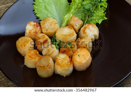 Baked scallops with sauce served salad leaves and thyme