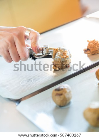 Baker is putting a scoop of cookies on tray close up