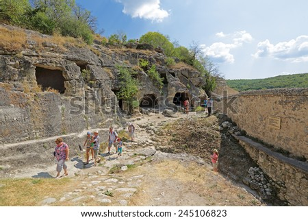 BAKHCHYSARAI, REPUBLIC OF CRIMEA, RUSSIA - AUG 12, 2014: Medieval cave city-fortress Chufut-Kale. Tourists near the southern (secret) gate