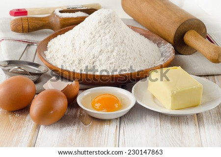 Baking ingredients - eggs, flour, sugar, butter on  wooden table