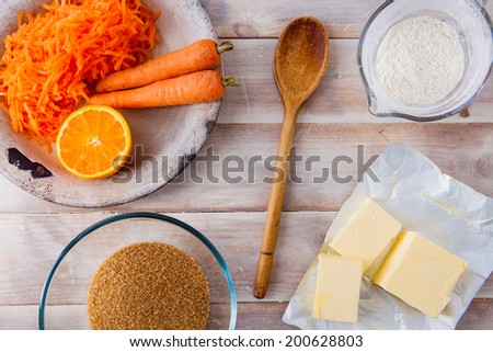 Baking ingredients for a carrot cake - flour, butter, brown sugar, grated carrots, half an orange, a wooden spoon on a rustic wooden background