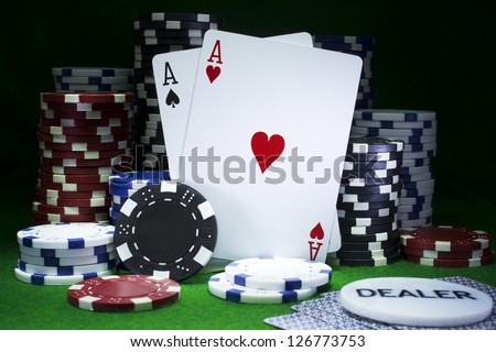Balancing pair of aces playing cards surrounded by poker chips on casino green felt. Gambling concept