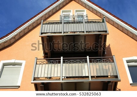Balcony of high-grade steel in Front of a peach colored gabled House
