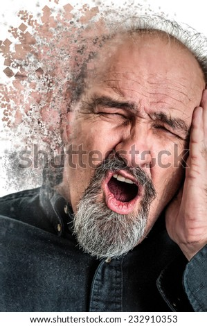 Balding man in his sixties holding his head in pain from a headache as he shouts.