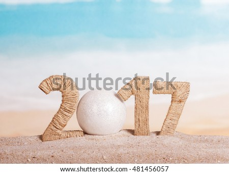 Ball instead of the number 0 in 2017 in the amount of sand on the sea background.