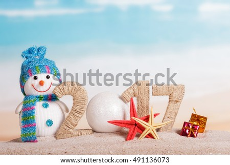 Ball instead of the number 0 in the amount of 2017, snowman, sea stars and Christmas gifts against the sea.