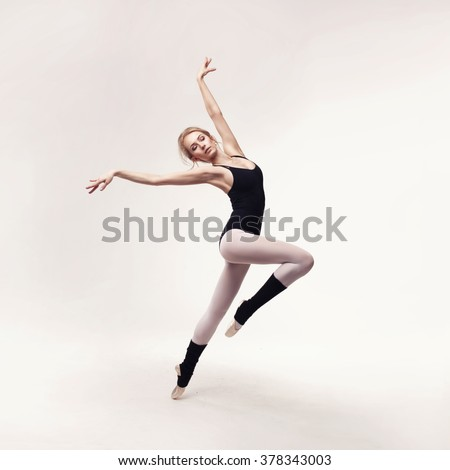 Ballerina in black outfit posing on toes over light grey studio background.