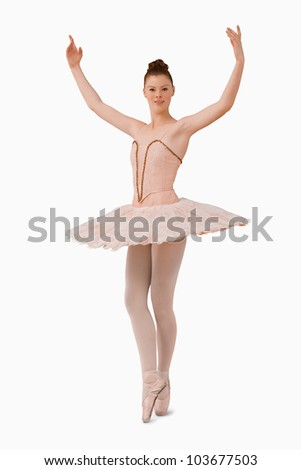 Ballerina with her arms risen against a white background