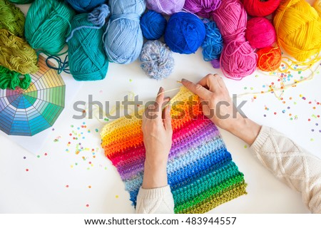Balls of colored yarn. View from above. All the colors of the rainbow. Sample knit. Women's hands are knitted. Crochet.