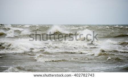 baltic beach in fall with clouds and waves towards deserted dunes. cloudy day