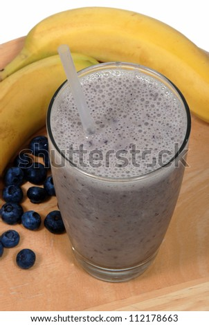 Banana, blueberry fruit smoothie in a glass near fresh, organic fruit