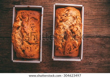 Banana Bread Loaf, Homemade Fresh Baked from Oven in Square Tin Pan, Wood Background, Vintage Country Rustic Still Life Style. Concept and Idea of Breakfast, Bakery. Top View.