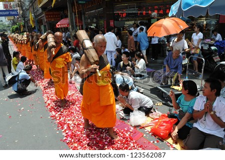 BANGKOK - APRIL 5: Devotees pay respect to monks from Wat Dhammakaya making a pilgrimage through central Bangkok to mark 2600 years since Buddha's enlightenment on April 5, 2012 in Bangkok, Thailand.