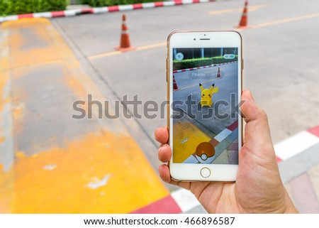 BANGKOK - AUGUST 9, 2016: Enthusiastic Pokemon player is catching Pikachu on street. The Pokemon Go has started craze in Thailand since August 6, 2016.
