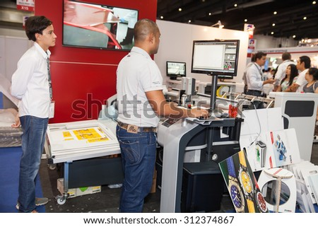 BANGKOK - AUGUST 29 :worker control cutting sticker machine at Pack Print and T-PLAS THAILAND on Aug 29,2015 in BITEC ,Bangkok, Thailand.