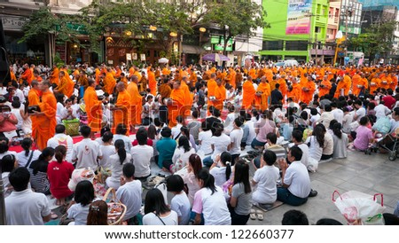 BANGKOK - DECEMBER 23: Participants at a mass alms giving at Soi Thonglor in celebration of the 2,600th anniversary of Lord Buddha's enlightenment on December 23, 2012 in Bangkok, Thailand.