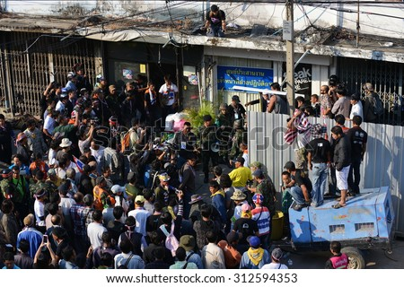 BANGKOK - JAN 17: Soldiers surrounded by protesters and media search a building after a bombing on anti government rally on Jan 17,  2014 in Bangkok, Thailand. A protester was killed in the attack.