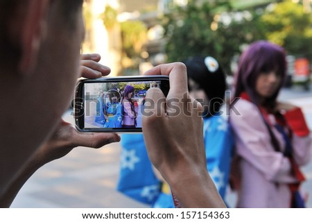 BANGKOK - MAR 31: A passerby uses a smartphone to capture cosplayers at a meet in Bangkok's shopping district on Mar 31, 2013 in Bangkok, Thailand. Japanese cosplay is popular with youth in Bangkok.