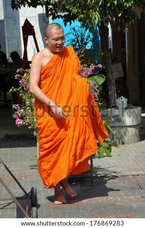 Bangkok, Thailand - December 17, 2011:  Buddhist monk in traditional orange robe walking bare-footed in a garden at Wat Hua Lamphong