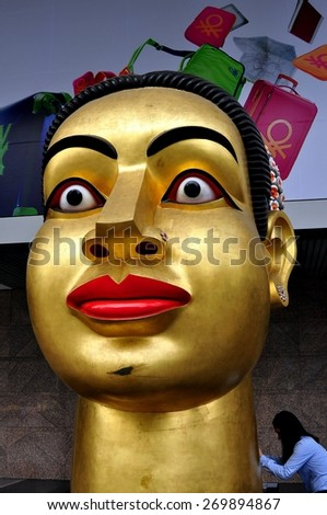 Bangkok, Thailand - January 23, 2013:  An enormous gilded contemporary bust of Buddha stands in front of the Central World shopping complex