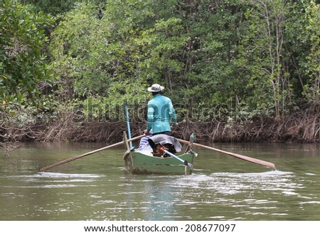 BANGKOK, THAILAND - MAY 14: Local Thai fishermen in their canoe amongst the mangrove forest near Tabla Mu Pier on the Khao Lak coastline, Bangkok, Thailand on the 14th May, 2014.