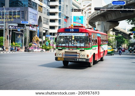 BANGKOK, THAILAND - 21 NOV 2013: Public transport bus passes crossroads street with skytrain track on background