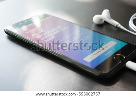 BANGKOK, THAILAND - NOVEMBER 25, 2016: Man using Iphone7 Plus jet black series choosing music from apple music store online