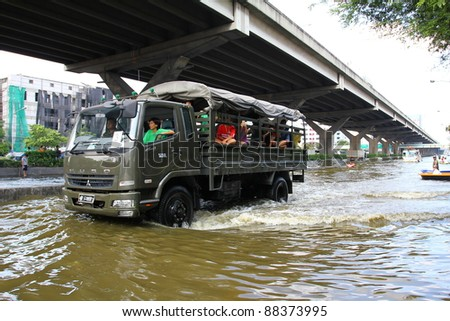 BANGKOK THAILAND - NOVEMBER 8 : Unidentified people sit in big truck to escape rising flood waters at Vipavadeerangsit Road suthisan junction, in Bangkok, Thailand on Nov. 8, 2011.