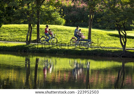 BANGKOK,THAILAND-OCTOBER 10, 2014: People ride bicycles in Jatujak Train Public Park,famous and celebrated public park in Bangkok.