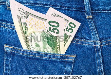 Banknotes of fifty U. S. dollars bill sticking out of the back jeans pocket
