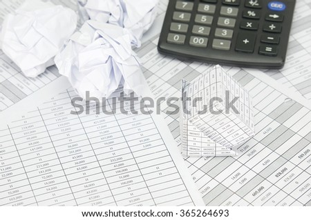 Bankruptcy of house and paper ball with calculator on finance account as background.