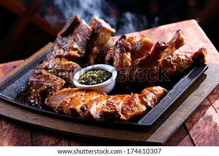 barbecued pieces of meat on a hot pan